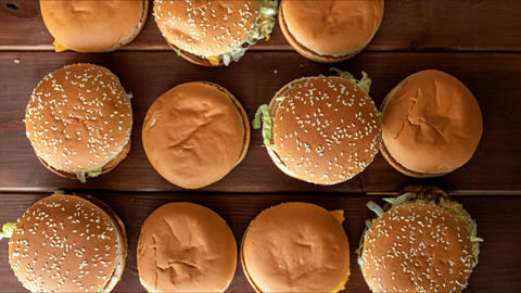 stop motion animation, burgers appearing on wooden table, heap of fast food Live Action