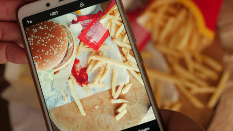 making, taking photograph of stack, heap of unhealthy food, fast food, top view Live Action
