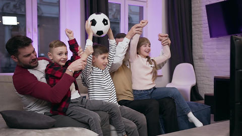 Agitated positive attractive family football fans sitting on the sofa at home Live Action