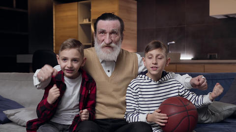 Good-looking elated positive mature granddad with beard and two satisfied teen Live Action