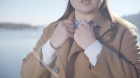 Unrecognizable young Caucasian woman fixing elegant beige coat on sunny autumn Live Action