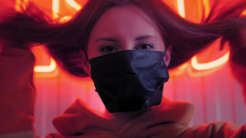 Young beautiful fashionable girl puts on a black medical mask. In a bar or club Live Action
