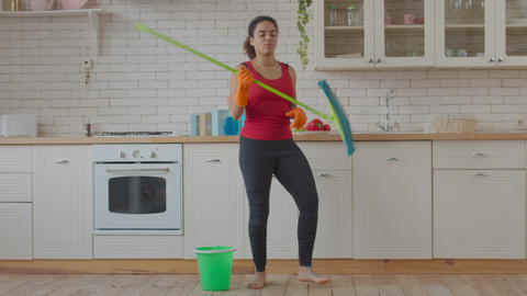 Woman dancing and singing with mop during cleanup Live Action