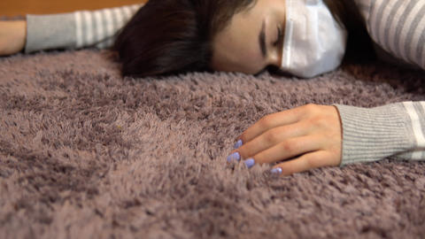 A young woman lies on the floor dead. A woman in a medical mask lies on the Live Action