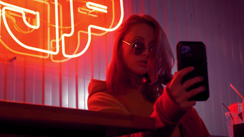 Trendy cute girl blogger in sunglasses taking selfie photo or video using Live Action