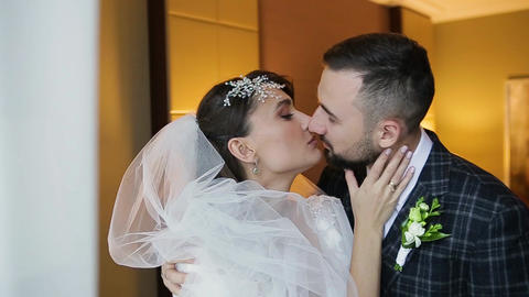 Close-up view of a happy wedding couple kissing in a luxury room of an expensive Live Action