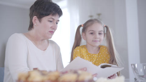 Adult brunette Caucasian woman and little girl discussing recipe of pancakes for Live Action