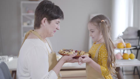 Side view of happy grandmother and granddaughter holding plate with baked tasty Live Action