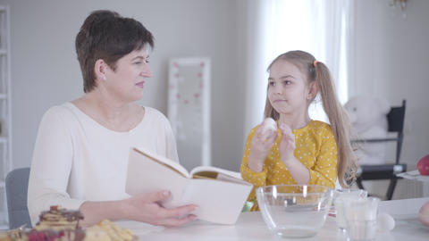 Cute Caucasian little girl gathering ingredients for pancakes as grandmother Live Action