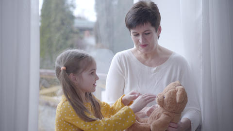 Portrait of smiling adult Caucasian woman playing teddy bear and talking with Live Action