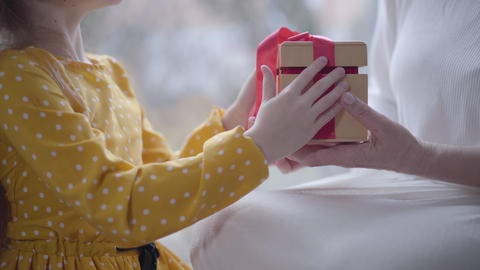 Unrecognizable Caucasian little girl giving present to elegant adult woman Live Action