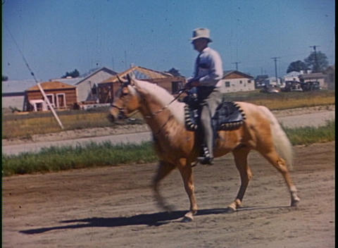 A man rides a horse in the suburbs in this color home movie Stock Video Footage