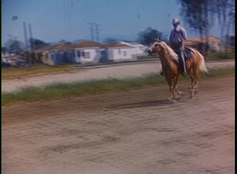 A man rides a horse in the suburbs in this color home movie Footage