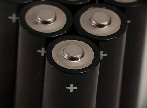 A closeup over a cluster of small batteries with plus signs Stock Video Footage