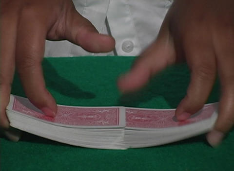 A casino dealer separates and shuffles a deck of cards Stock Video Footage