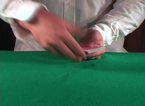 A shot of a dealer tossing cards from a deck towards camera Footage