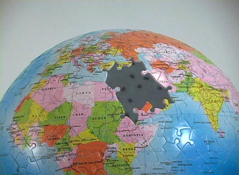 A world globe puzzle has the Middle East pieces missing Footage