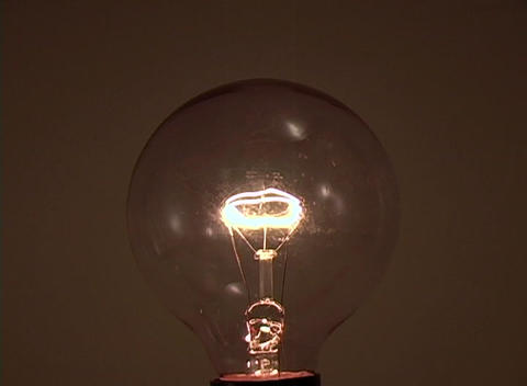A light bulb slowly extinguishes Stock Video Footage