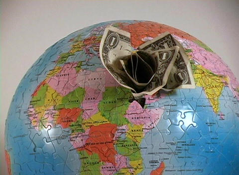 An earth puzzle has dollar bills stuck into a hole where the Middle East is located Footage