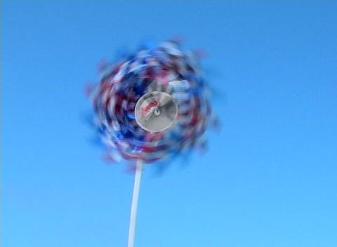 A red white and blue patriotic pinwheel spins in the wind... Stock Video Footage