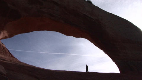 A person walks beneath a giant sandstone arch in Arches National Park, Utah Footage