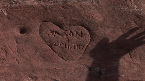 The shadow of a hand moves over a graffiti heart carved... Stock Video Footage