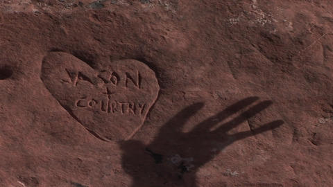 The shadow of a hand moves over a graffiti heart carved into sandstone Footage