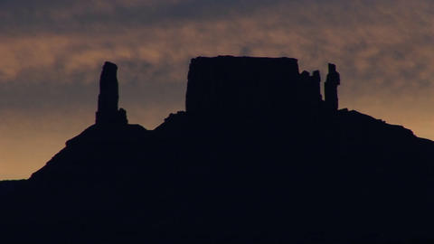 A horizon of desert buttes and rock formations is silhouetted at golden-hour Footage