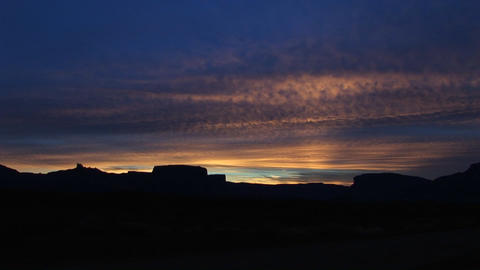 A dark sky silhouettes desert buttes and rock formations in the American Southwest Footage