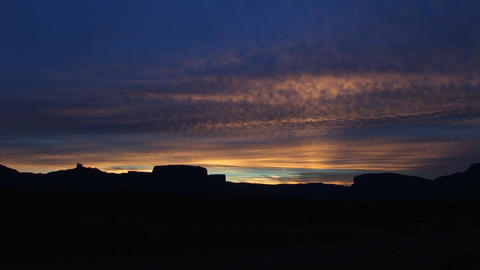 A dark sky silhouettes desert buttes and rock formations... Stock Video Footage