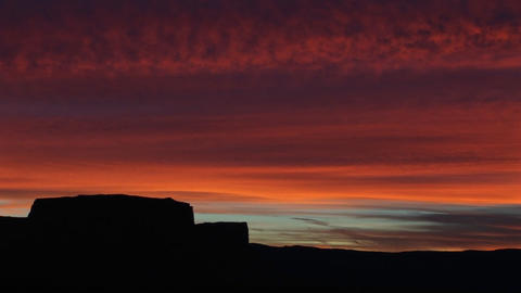 A horizon of desert buttes and rock formations is silhouetted against a brilliant golden-hour sky Live Action