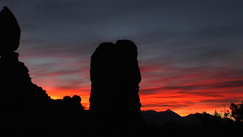 A red and blue sky silhouettes rock formations in Arches... Stock Video Footage