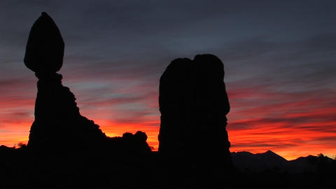 A red and blue sky silhouettes rock formations in Arches National Park, Utah Footage