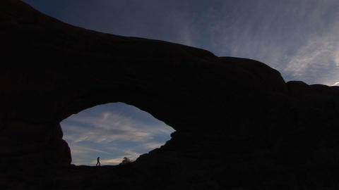 A hiker walks beneath an arch at Arches National Park, Utah Footage