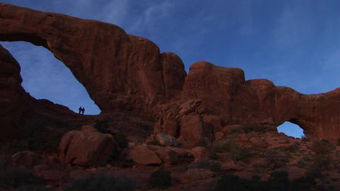 Hikers stand beneath an arch at Arches National Park, Utah Footage