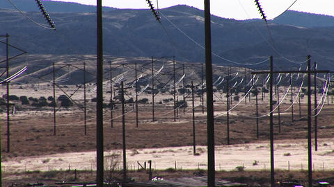 Pan-right across electrical power lines run across a Western landscape Footage