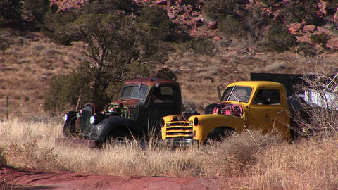 Medium shot of two old trucks abandoned in a field Stock Video Footage