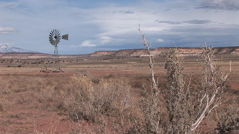 Long shot of an old windmill standing out in a desert plain Stock Video Footage