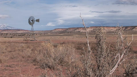 Long shot of an old windmill standing out in a desert plain Footage