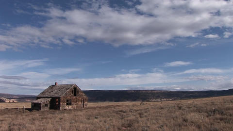 Long shot of an old abandoned homestead on a lonely prairie Footage