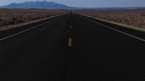 Pan-up slowly to an empty highway stretching through the desert Footage