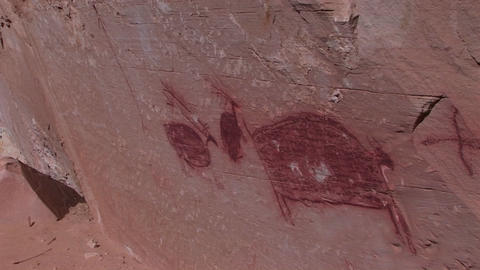 Pan-right slowly across the face of a cliff to an American Indian pictograph Footage