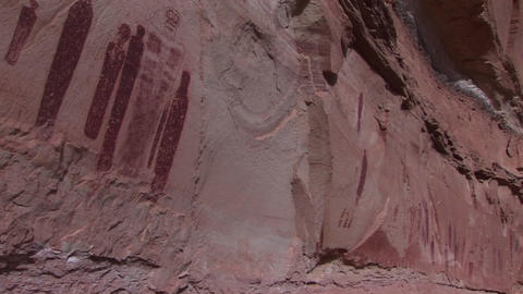 Pan-left across American Indian petroglyphs on a canyon wall Footage