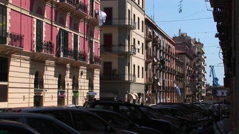 Stone and wood buildings are in the background of cars parked in the shade Palermo, Italy Footage