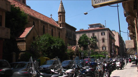 Motorcycles are lined near a sidewalk and old architecture Palermo, Italy Footage