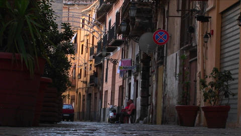 A man sits in a chair outside apartment buildings as pedestrians walk down the street Palermo, Italy Footage