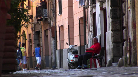A man sits in a chair outside apartment buildings as... Stock Video Footage