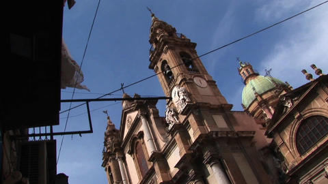 A low dutch angle of a religious building below a cloudy blue sky Palermo, Italy Footage