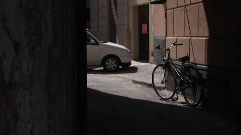 A shadow frames a bicycle and car near a rock building... Stock Video Footage