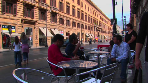 Patrons sit at tables next to a busy street and across... Stock Video Footage
